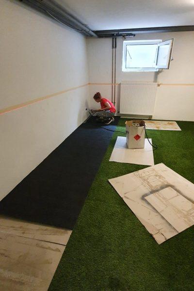 Aufbringen des Sprühklebers an die Wand und Kunstrasenstreifen